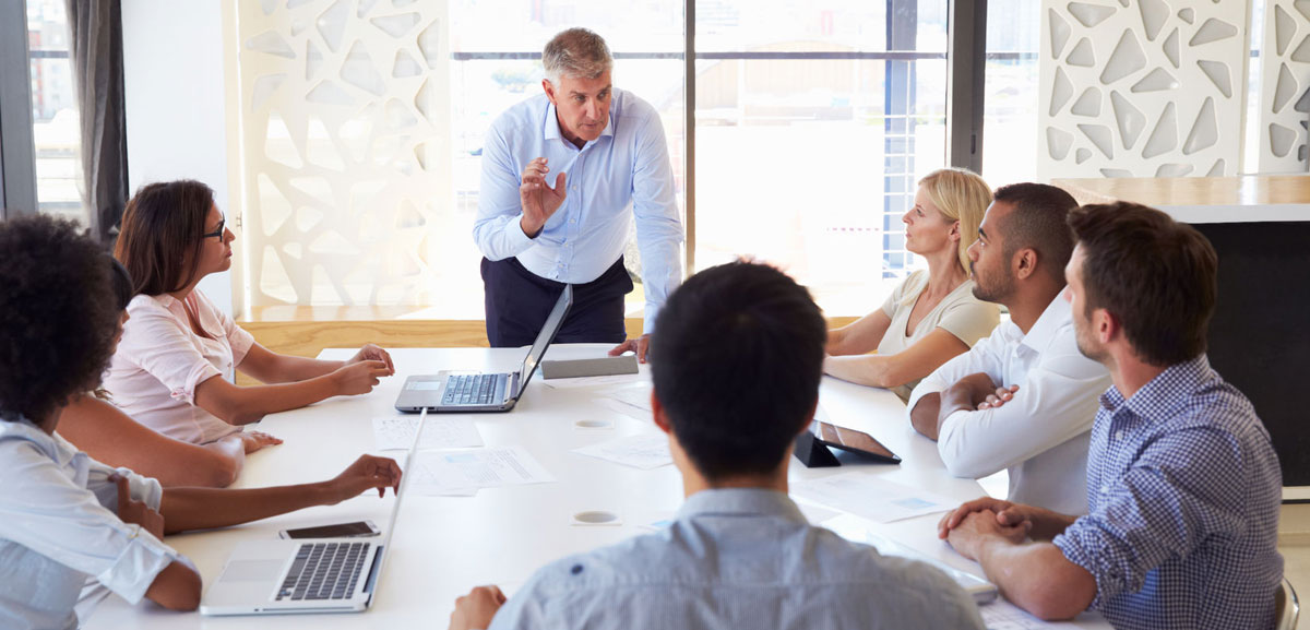 Group of people in boardroom discussing IT and their business