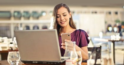 Young woman using two-factor authentication on her laptop and phone