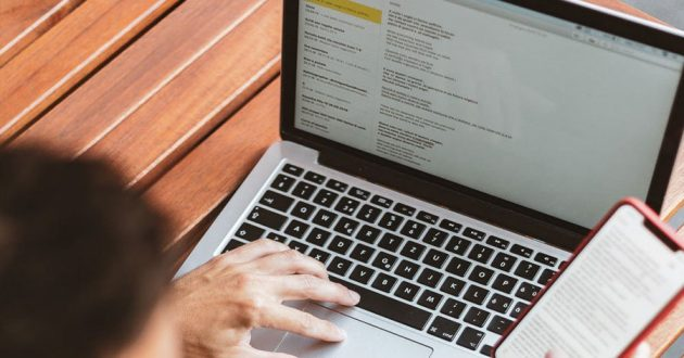 Man checking email on laptop and phone