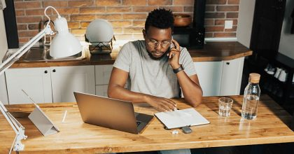 Man sitting at desk on the phone working from home